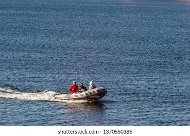 New Bedford, Massachusetts, USA - April 11, 2019: Three people taking a chilly ride on the Acushnet River in an inflatable boat in early spring