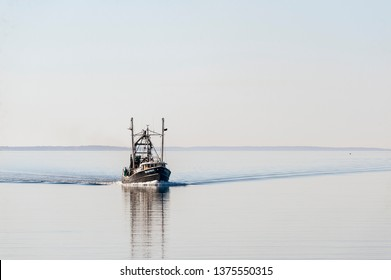 New Bedford, Massachusetts, USA - April 7, 2019:  Commercial fishing boat Enterprise, hailing port Cape May, New Jersey, heading into New Bedford from Buzzards Bay on early spring morning