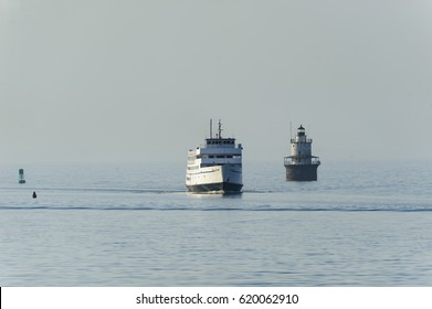 New Bedford, Massachusetts, USA - April 12, 2017: Block Island ferry M.V. Carol Jean passing Butlers Flat lighthouse in New Bedford harbor on hazy morning