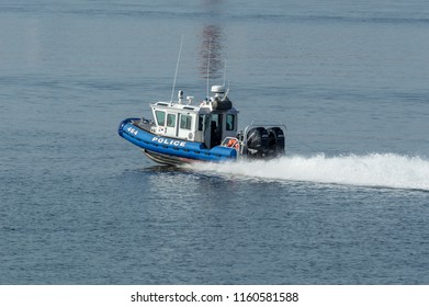 New Bedford, Massachusetts, USA - August 17, 2018: Twin 250-horsepower outboards driving Fairhaven Police Department patrol boat toward Buzzards Bay