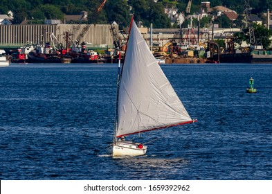 New Bedford, Massachusetts, USA  - August 9, 2019: Brisk wind from the northwest pushing sailboat south in New Bedford inner harbor