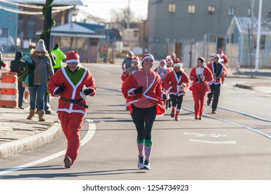 New Bedford, Massachusetts, USA - December 8, 2018: Santa wearing a big smile as she heads for the finish of the Santa Sightings 5K Fun Run along the New Bedford waterfront