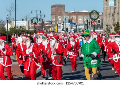 New Bedford, Massachusetts, USA - December 8, 2018: Runner with an individualistic streak surfaces in crowd of Santas near the start of the Santa Sightings 5K Fun Run along the New Bedford waterfront