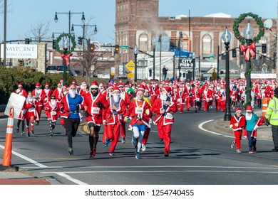 New Bedford, Massachusetts, USA - December 8, 2018: Hundreds of Santas on the move near the start of the Santa Sightings 5K Fun Run along the New Bedford waterfront on a very chilly afternoon