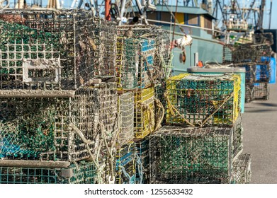 New Bedford, Massachusetts, USA - December 8, 2018: Grungy lobster traps stacked at Leonard's Wharf after season underwater