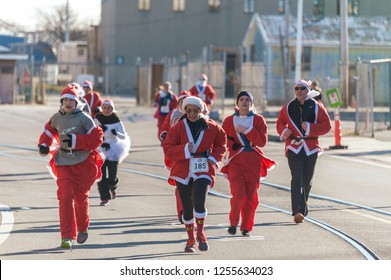 New Bedford, Massachusetts, USA - December 8, 2018: Group of Santas fight a chilly head wind heading for the finish of the Santa Sightings 5K Fun Run along the New Bedford waterfront