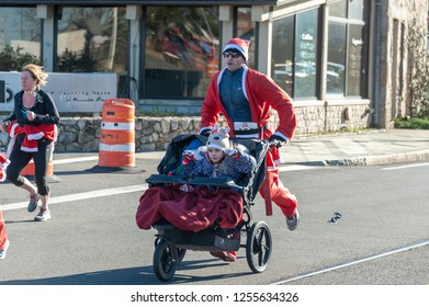 New Bedford, Massachusetts, USA - December 8, 2018: One child looking for gold, the other taking a snooze as they head for the finish of the Santa Sightings 5K Fun Run on the New Bedford waterfront