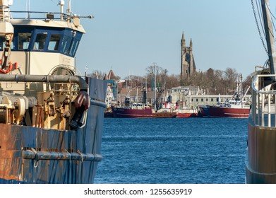 New Bedford, Massachusetts, USA - December 8, 2018: Commercial fishing boats on the New Bedford waterfront frame the tower of the Unitarian Church in Fairhaven