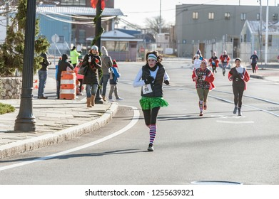 New Bedford, Massachusetts, USA - December 8, 2018: Runners strung out along MacArthur Blvd. as they head for the finish of the Santa Sightings 5K Fun Run on the New Bedford waterfront