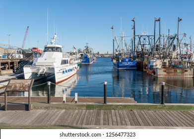 New Bedford, Massachusetts, USA - December 8, 2018: Commercial vessels on the New Bedford waterfront with Fairhaven skyline in distance
