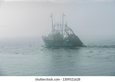 New Bedford, Massachusetts, USA - February 5, 2019: Commercial fishing vessel New Sea Rover fading in the fog on winter morning