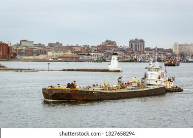 New Bedford, Massachusetts, USA - February 11, 2018: Tug Sirius pushing the double-hulled fuel barge Meropa 900 out of New Bedford harbor with lighthouse in background