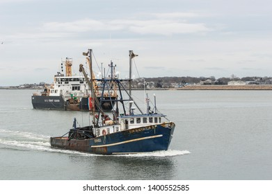 New Bedford, Massachusetts, USA - February 12, 2019: Commercial fishing vessel Tom Slaughter II and U.S. Coast Guard vessel Ida Lewis approaching hurricane barrier on winter morning