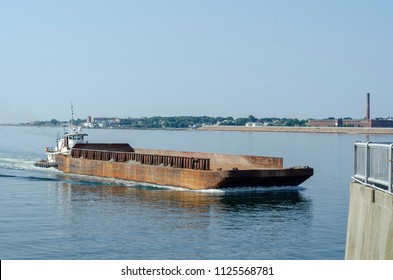 New Bedford, Massachusetts, USA - July 2, 2018: Tug Sirius approaching New Bedford hurricane barrier pushing empty barge