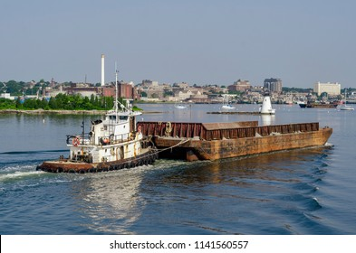 New Bedford, Massachusetts, USA - July 2, 2018: Tug Sirius pushing empty barge past Palmer Island Light Station in New Bedford harbor