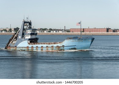 New Bedford, Massachusetts, USA - July 9, 2019: Clammer Sea Watcher 1, hailing port Atlantic City, New Jersey, nearing New Bedford with factories and tenements in background