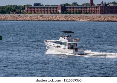 New Bedford, Massachusetts, USA – July 27, 2019: Motor yacht Pappy's Retreat, hailing port Plymouth, MA, cruising across New Bedford outer harbor with hurricane barrier and factory in background
