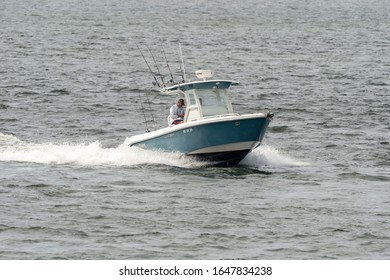 New Bedford, Massachusetts, USA – July 17, 2019: Powerboat bristling with fishing poles running across New Bedford outer harbor