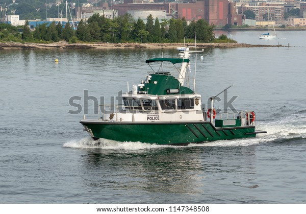 New Bedford, Massachusetts, USA - July 31, 2018: Massachusetts Environmental Police patrol boat crossing New Bedford inner harbor