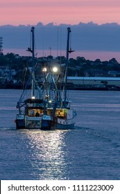 New Bedford, Massachusetts, USA - June 11, 2018: Commercial fishing vessel Starbrite, hailing port Cape May, New Jersey, crossing New Bedford inner harbor at dawn