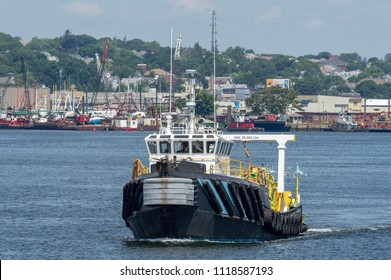 New Bedford, Massachusetts, USA - June 22, 2018:  Work boat Northstar Commander, hailing port Cape May, New Jersey, on Acushnet River with New Bedford waterfront in background