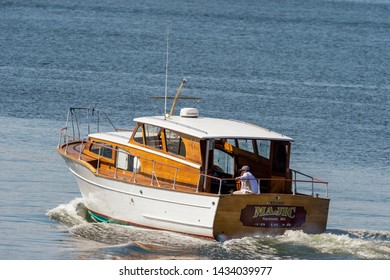 New Bedford, Massachusetts, USA - June 24, 2019: Classically styled cabin cruiser Majic sets out from New Bedford