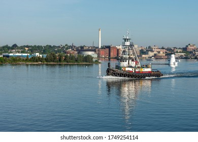 New Bedford, Massachusetts, USA - June 4, 2020: Tug Realist passing lighthouse on her way out of New Bedford