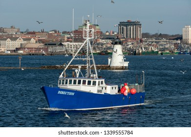 New Bedford, Massachusetts, USA - March 12, 2019: Commercial fishing vessel Direction leaving New Bedford on winter morning with gulls circling