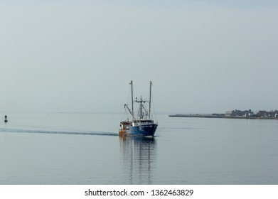 New Bedford, Massachusetts, USA - March 30, 2019: Commercial fishing boat Blue Wave coming out of foggy Buzzards Bay, returning to New Bedford on early spring morning