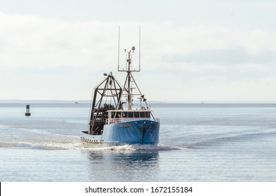 New Bedford, Massachusetts, USA - March 12, 2020: Clammer Timberline I crossing New Bedford outer harbor on hazy morning