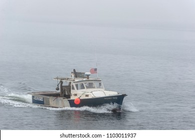 New Bedford, Massachusetts, USA - May 31, 2018: Lobster boat Honi-Do approaching hurricane barrier on foggy morning
