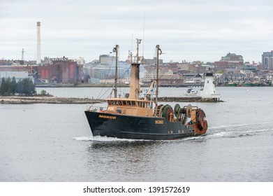 New Bedford, Massachusetts, USA - May 2, 2019: Commercial fishing vessel Morue heading down the Acushnet River, passing the decommissioned Palmer Island Light Station