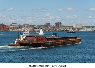 New Bedford, Massachusetts, USA - May 8, 2019: Tug Sirius pushing barge up Acushnet River with lighthouse and New Bedford waterfront in background