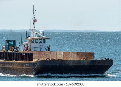 New Bedford, Massachusetts, USA - May 8, 2019: Tug Sirius pushing barge across New Bedford outer harbor