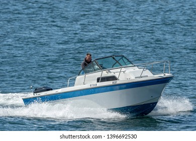 New Bedford, Massachusetts, USA - May 8, 2019: Man in small cabin cruiser  crossing New Bedford outer harbor near hurricane barrier