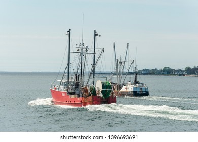 New Bedford, Massachusetts, USA - May 8, 2019: Dragger Mary K easing past fishing vessel Discovery  crossing New Bedford outer harbor