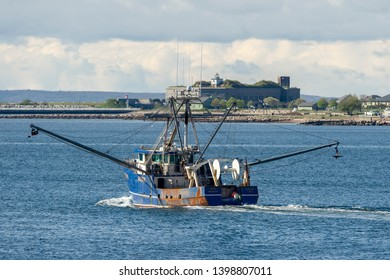New Bedford, Massachusetts, USA - May 15, 2019: Commercial fishing boat Miss Madeline, hailing port Cape May New Jersey, dropping her outriggers as she leaves New Bedford