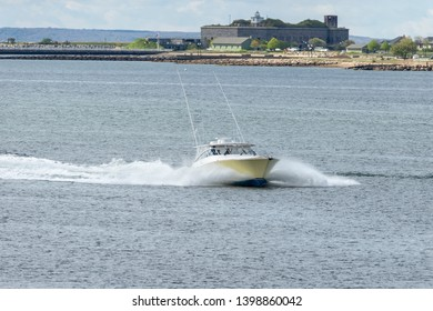 New Bedford, Massachusetts, USA - May 15, 2019: Powerboat Lucky Penny, hailing port Ft. Lauderdale, Florida, passing Fort Taber while heading up the Acushnet River