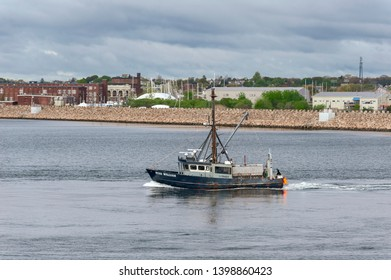 New Bedford, Massachusetts, USA - May 15, 2019: Commercial fishing vessel Ryan William leaving New Bedford under cloudy skies