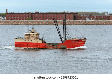 New Bedford, Massachusetts, USA - May 13, 2019: Eastern-rigged commercial fishing vessel Explorer  crossing New Bedford outer harbor