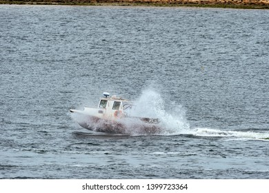 New Bedford, Massachusetts, USA - May 13, 2019: Lobster boat banging through wake on its way across New Bedford outer harbor