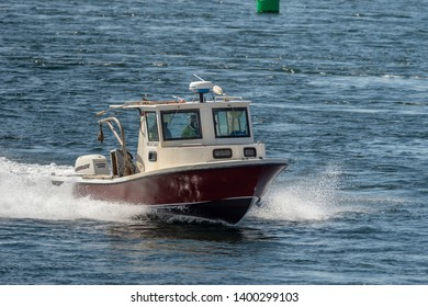 New Bedford, Massachusetts, USA - May 16, 2019: Lobster boat cruising across chop in New Bedford outer harbor