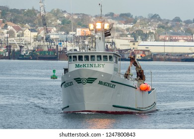 New Bedford, Massachusetts, USA -  November 1, 2017: Work lights glow on boat and water as commercial fishing vessel McKinley leaves New Bedford
