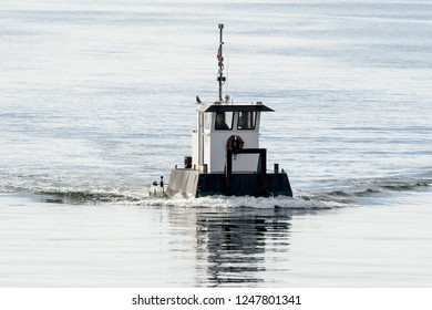 New Bedford, Massachusetts, USA -  November 1, 2017: Tiny workboat Can-Do from Cuttyhunk approaching New Bedford hurricane barrier on Acushnet River