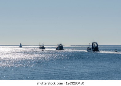 New Bedford, Massachusetts, USA - November 4, 2018: Commercial fishing vessels Lady Brittany, Sea Watcher I and Sea Watcher II heading into Buzzards Bay with Butler's Flat Light Station in background