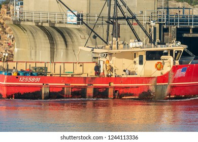 New Bedford, Massachusetts, USA - October 23, 2017: Fishermen working aboard fishing boat Liberty as the vessel transits the hurricane barrier