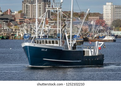 New Bedford, Massachusetts, USA - October 31, 2018: Commercial fishing vessel Selje crossing harbor with New Bedford waterfront in background