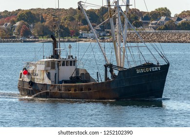 New Bedford, Massachusetts, USA - October 31, 2018: Commercial fishing vessel Discovery crossing New Bedford outer harbor with hurricane barrier in background