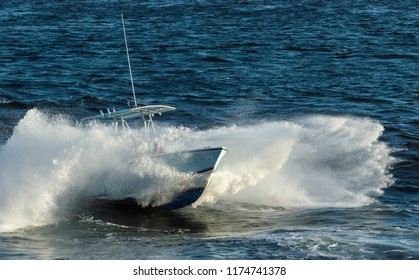New Bedford, Massachusetts, USA - September 5, 2018: Powerboat generates plenty of whitewater hitting chop in New Bedford outer harbor