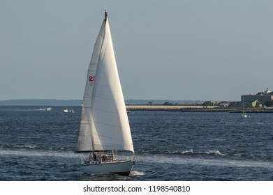 New Bedford, Massachusetts, USA - September 2, 2018: Evening sun reflecting off sails of sailboat crossing New Bedford outer harbor